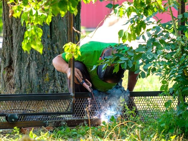 Pracownik spawa metal za pomocą spawania łukiem elektrycznym