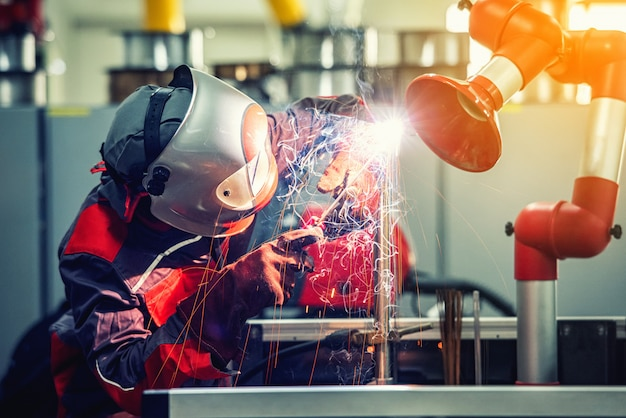 Pracownik spawacza przemysłowego spawa metalową część fabrycznie maską ochronną