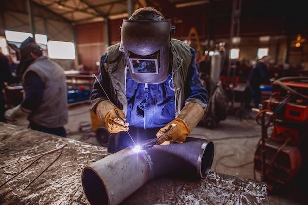 Pracownik spawalniczy. kombinezon ochronny i maska na sobie. wnętrze warsztatu.