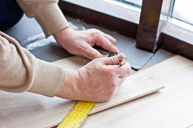 Pracownik sporządza znaczniki dotyczące układania podłóg laminowanych