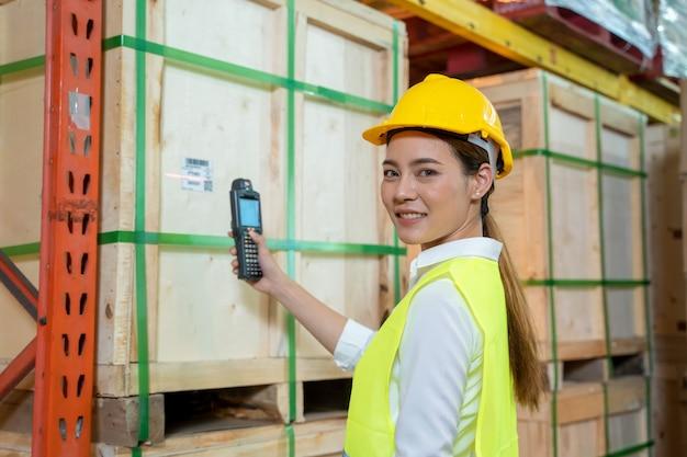Pracownik sprawdza i skanuje paczki za pomocą laserowego skanera kodów kreskowych w dużym magazynie, koncepcji logistycznej i eksportowej.