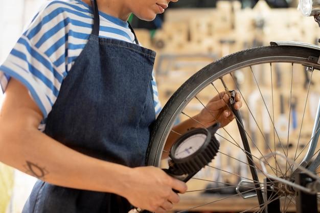 Pracownik sprawdzający koło rowerowe z bliska