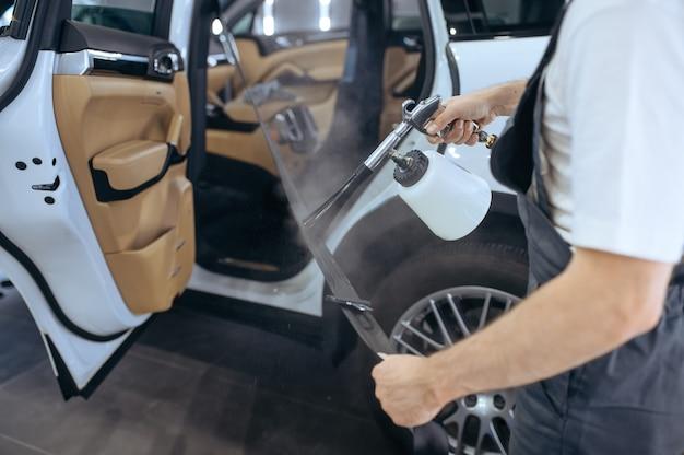 Pracownik spryskuje samochodowe pasy bezpieczeństwa, pranie chemiczne i detale