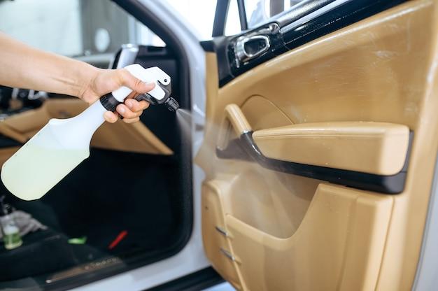 Pracownik spryskuje tapicerkę drzwi samochodu, pranie chemiczne i detale