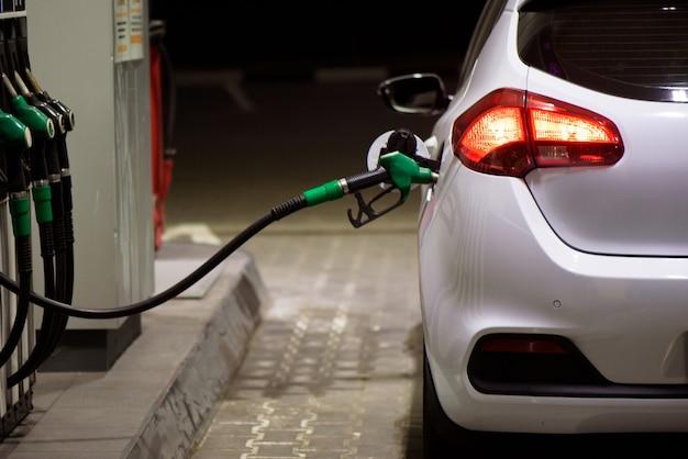Pracownik stacji benzynowej w odzieży roboczej tankowania luksusowego samochodu benzyną, trzymając pistolet do napełniania na stacji.