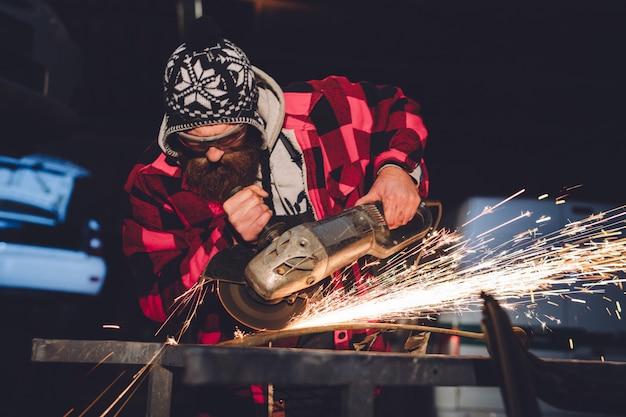 Pracownik stacji serwisowej wykonuje naprawy nadwozia za pomocą spawarki w ręku iskier