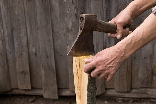 Pracownik, starszy mężczyzna ze starym toporem rąbie drewno na opał.