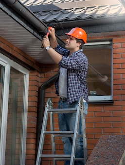 Pracownik stojący na drabinie i naprawiający rynnę w domu