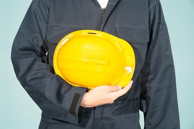 Pracownik stojący w niebieskim kombinezonie trzymając żółty kask na białym tle na niebieskim tle