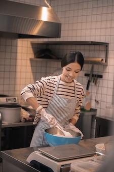 Pracownik stołówki. promieniejący ciemnowłosy młody, atrakcyjny pracownik małej kafeterii gotującej w kuchni