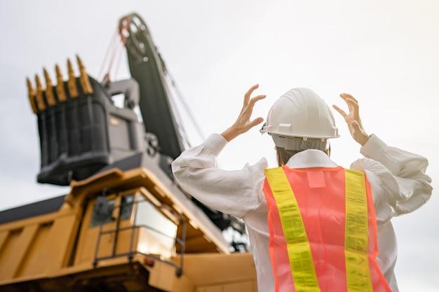Pracownik stresujący przy wydobyciu węgla brunatnego lub węgla z ciężarówką przewożącą węgiel.