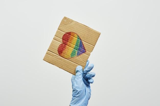 Pracownik systemu opieki zdrowotnej trzymający ręcznie robioną tabliczkę z flagą lgbt miejscem na kopię