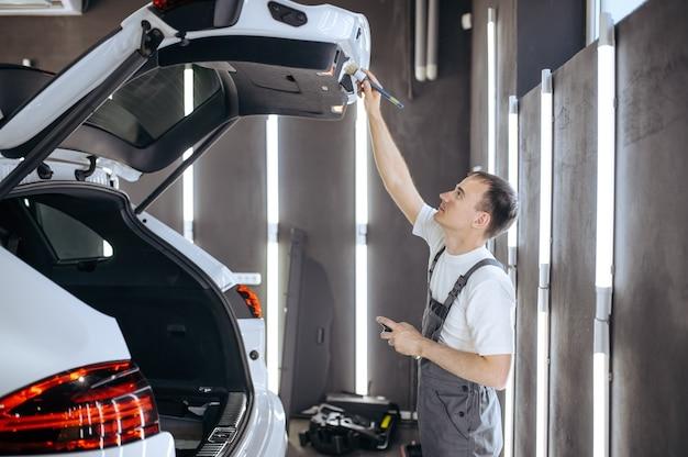 Pracownik szczotką wyciera drzwi bagażnika samochodu, czyści chemicznie i detaluje