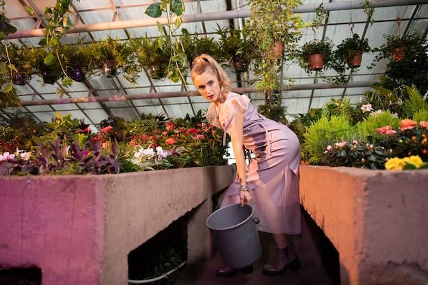 Pracownik szklarni. miła młoda kobieta stojąca z wiadrem podczas pracy w szklarni