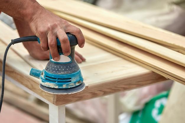 Pracownik szlifierki poleruje drewnianą deskę. deski szlifierskie orbitalna maszyna mimośrodowa.