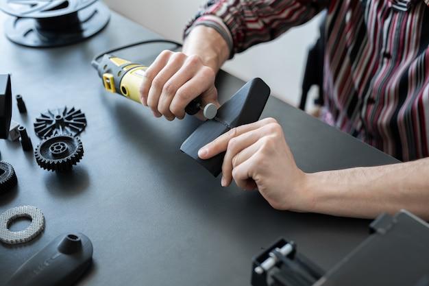 Pracownik szlifuje gotową część drukarki 3d