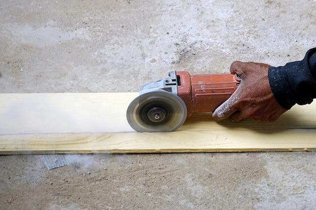 Pracownik szlifuje twardą podłogę pracownik z szlifierką o wysokim ścinaniu tnie sztuczne drewno