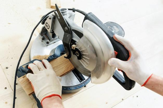 Pracownik tnie drewniane deski podłogowe za pomocą piły tarczowej