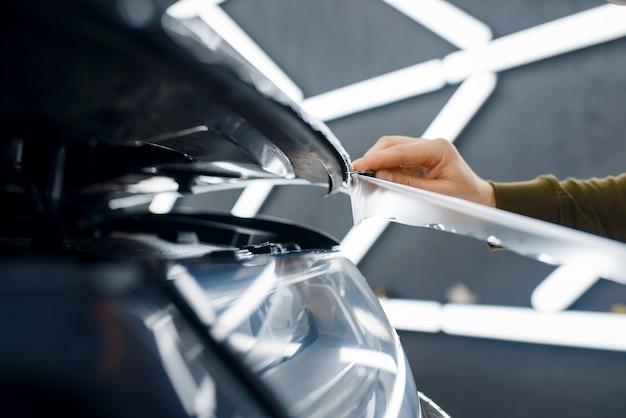 Pracownik tnie przezroczystą folię ochronną na masce samochodu. montaż powłoki chroniącej lakier samochodu przed zarysowaniami. nowy pojazd w garażu, autotuning