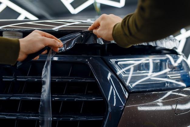 Pracownik tnie przezroczystą folię ochronną na masce samochodu. montaż powłoki chroniącej lakier samochodu przed zarysowaniami. nowy pojazd w garażu, procedura tuningu