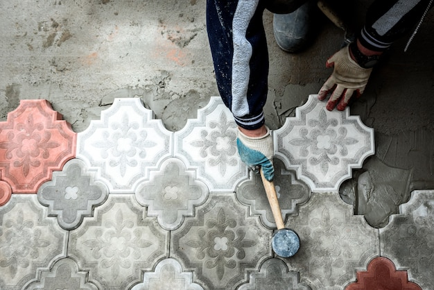 Pracownik trzyma betonową płytkę chodnikową. koncepcja pracy przy układaniu figurowych ozdobnych płyt chodnikowych.