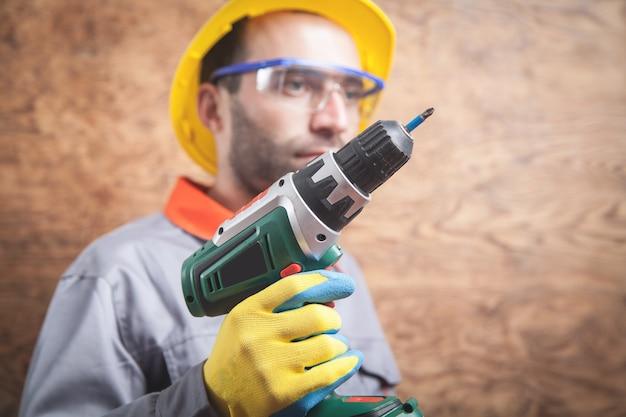 Pracownik trzymając wkrętarkę akumulatorową na drewnianej ścianie