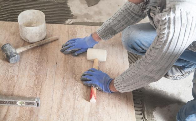 Pracownik trzymający młotek gumowy. układanie podłogowych płytek ceramicznych. renowacja podłogi