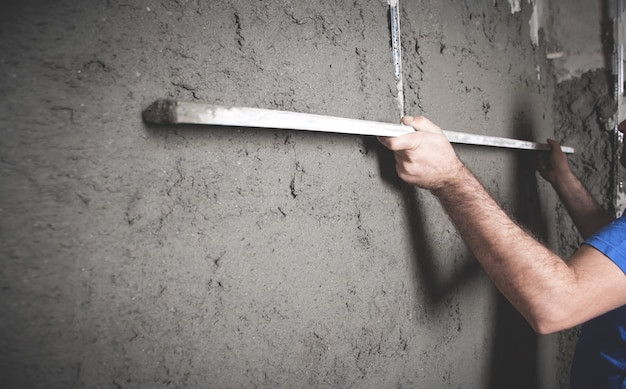 Pracownik trzymający poziom narzędzia tynkowanie ścian roboty budowlane praca dom przemysł