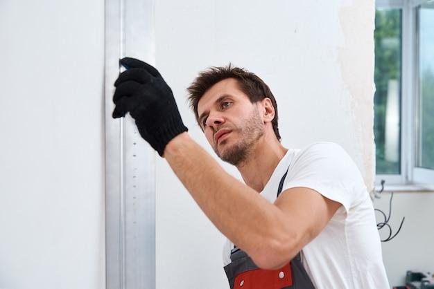 Pracownik tynkujący ścianę za pomocą długiej szpatułki.
