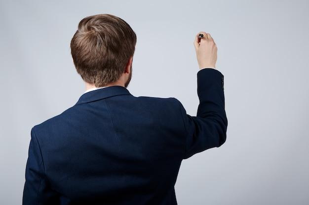 Pracownik ubrany w białą koszulę i ścianę garnituru, z bliska, koncepcja biznesowa, trzyma pióro i pisze na biurku.