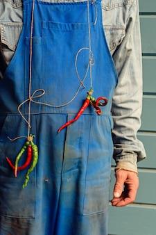 Pracownik ubrany w brudny kombinezon z garścią gorzkiego pieprzu na szyi dobry humor