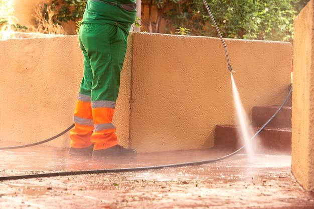 Pracownik ubrany w zieloną odzież roboczą, sprzątający ulice w celu zapobiegania wirusowi covid19 lub koronawirusem za pomocą pistoletu na wodę z wybielaczem pod ciśnieniem