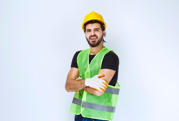 Pracownik ubrany w żółty kask i rękawice warsztatowe.