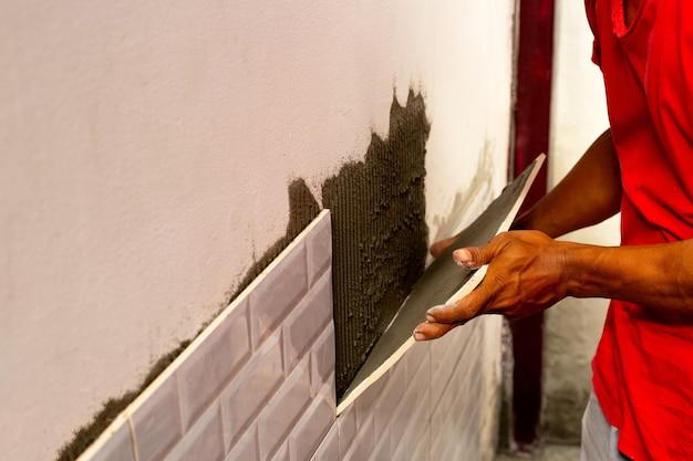 Pracownik układający płytki na ścianie.