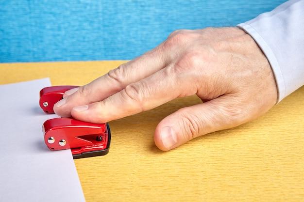 Pracownik umysłowy wybijanie otworów w arkuszu papieru, używając czerwonego dziurkacza.