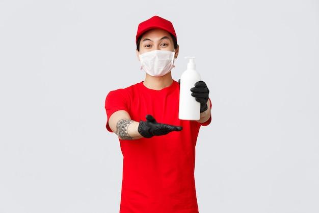Pracownik usługi dostawy, dając klientowi środek do dezynfekcji rąk. wesoły kurier trzyma środek dezynfekujący, nosi maskę medyczną i rękawice ochronne podczas samokwarantanny covid-19, dostarcza zamówienia podczas pandemii.