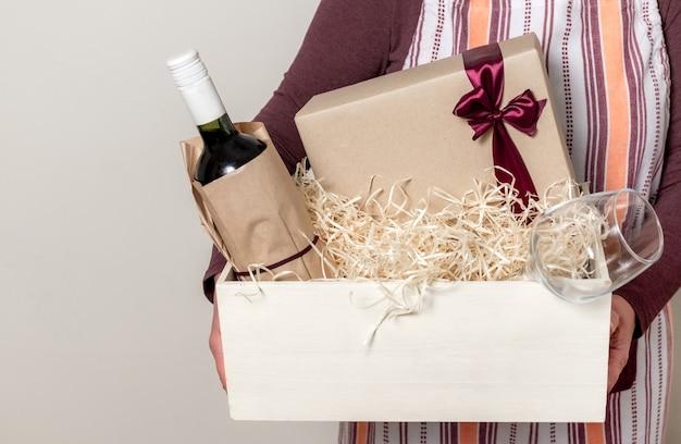 Pracownik usługi dostawy pakowanie butelki wina i prezentów do pudełka ze słomką dla klienta.