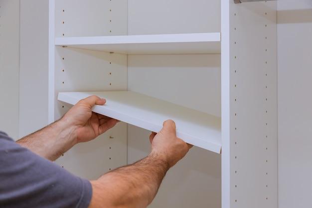 Pracownik ustawia półkę do szafy