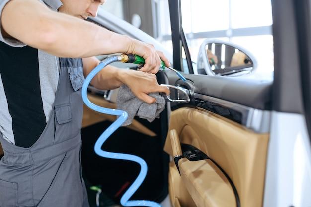 Pracownik usuwa brud za pomocą powietrza, czyszczenia samochodu na sucho i detali