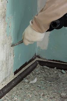 Pracownik usuwa starą farbę z betonowej ściany młotkiem obrotowym z dłutem, mechaniczną metodą usuwania farby, prace naprawcze w mieszkaniu