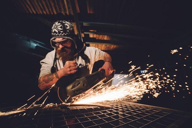 Pracownik używa szlifierki kątowej w fabryce i rzuca iskry