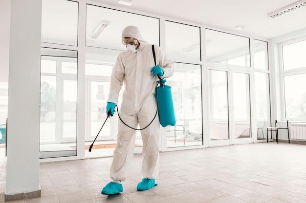 Pracownik w białym sterylnym mundurze, z gumowymi rękawiczkami i maską trzymający rozpylacz ze środkiem dezynfekującym i sterylizującym.