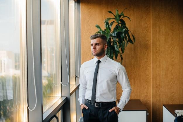 Pracownik w biurze stoi przy oknie. finanse
