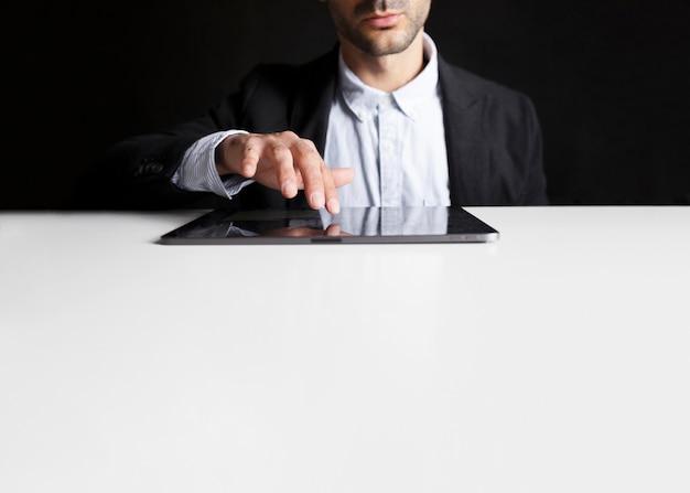 Pracownik w biurze za pomocą tabletu na czarno-biały