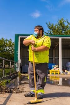 Pracownik w fabryce recyklingu lub czystym punkcie i śmieciach z maską na twarz i zabezpieczeniami. portret pracownika z miotłą
