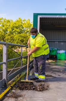 Pracownik w fabryce recyklingu lub czystym punkcie i śmieciach z maską na twarz i zabezpieczeniami. zamiatanie wnętrza obudowy