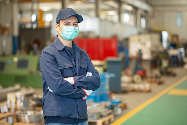 Pracownik w fabryce w masce podczas pandemii koronawirusa covid-19