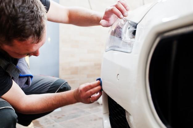 Pracownik w garażu detailingowym umieścił poliuretanową osłonę z folii przeciw żwirowej w białym luksusowym aucie.