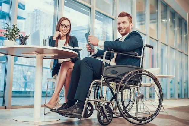 Pracownik w garniturze na wózku inwalidzkim z tabletem w biurze.