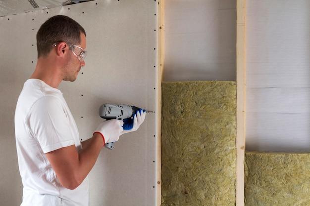 Pracownik w goglach ze śrubokrętem pracujący na izolacji. płyta gipsowo-kartonowa na belkach ściennych, izolacja łat z wełny mineralnej w drewnianej ramie. komfortowy ciepły dom, ekonomia, koncepcja budowy i remontu.